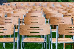 Wooden chairs stand outside in the park in the rain. Empty auditorium, green grass, waterdrops, closeup. Lot of wooden chairs stand outside in the park in the royalty free stock photo
