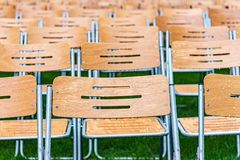 Wooden chairs stand outside in the park in the rain. Empty auditorium, green grass, waterdrops, closeup. Lot of wooden chairs stand outside in the park in the stock photo