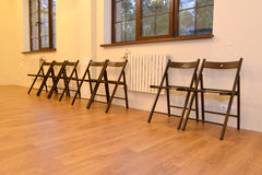 Wooden chairs stand in a row along a wall in the hall. Interior Royalty Free Stock Images