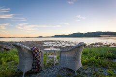Wooden chairs at sunset on beach Stock Photo