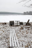 Wooden chairs and table at frozen lake Stock Photos