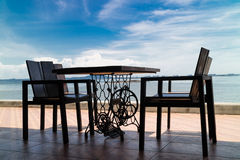 Wooden chairs and table on sea terrace restaurant against sunlig Royalty Free Stock Photos