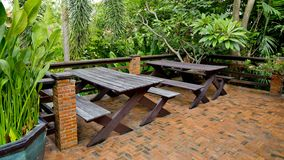 Wooden chairs and table set at balcony in a green plant garden. Stock Photo