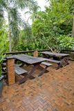 Wooden chairs and table set at balcony in a green plant garden. Royalty Free Stock Photography