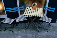 Wooden chairs and table standing outside a cafe. Three wooden chairs and a table on the street next to a cafe window with flowers stock photos