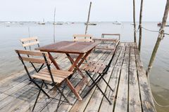Wooden chairs and tables installed on a pontoon at the edge of the arcachon royalty free stock photos
