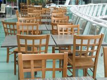 Wooden chairs and tables of a restaurant seating outside stock photos