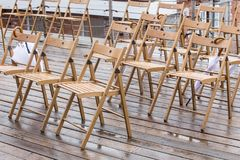 Wooden chairs and umbrellas in the rain. Outside Stock Photos