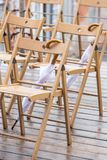 Wooden chairs and umbrellas in the rain. Outside Royalty Free Stock Image