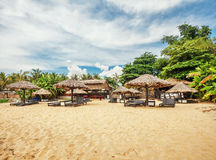 Wooden chairs and umbrellas on sand beach Stock Photography