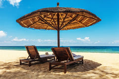Wooden chairs and umbrellas on white sand beach Royalty Free Stock Photos