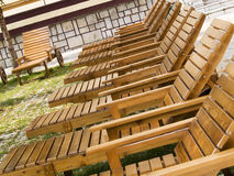 Wooden chaise-longues. In hotel garden stock photos