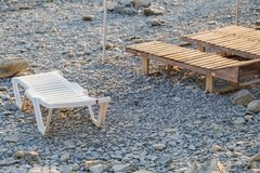 Wooden chaise lounge on the beach on a sunny day. Wooden chaise lounge on the beach on a sunny day royalty free stock photo