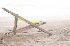 Wooden chaise lounge on a soft white background on beach stock photography