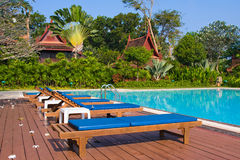 Wooden chaise lounges on the bank of pool. Thailand royalty free stock photo
