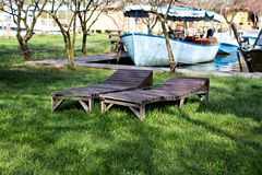Wooden chaise lounges on green grass. Time for rest, summer vacation, relaxation royalty free stock image