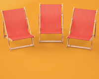 Wooden chaise lounges on orange background Royalty Free Stock Photos