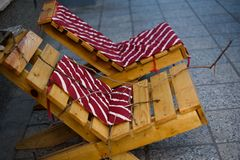 Wooden chaise lounges with red pillows. Sun loungers on the stre