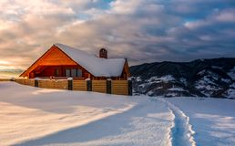 Wooden chalet in deep snow at sunrise. Path to wooden chalet in deep snow at sunrise. gorgeous landscape in winter mountains, great place for vacation Stock Photos