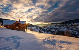 Wooden chalet in deep snow at sunrise. Wooden chalet in village outskirts at sunrise. gorgeous landscape in winter Carpathian mountains, great place for vacation Stock Image