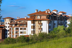 Wooden chalet hotel houses and summer mountains panorama in bulgarian ski resort Bansko, Bulgaria Royalty Free Stock Photo