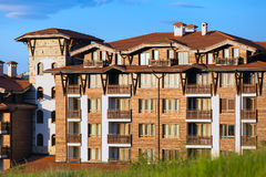 Wooden chalet hotel houses and summer mountains panorama in bulgarian ski resort Bansko, Bulgaria Royalty Free Stock Photos