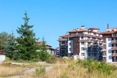 Wooden chalet hotel houses and summer mountains panorama in bulgarian ski resort Bansko, Bulgaria Royalty Free Stock Image