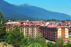 Wooden chalet hotel houses and summer mountains panorama in bulgarian ski resort Bansko, Bulgaria Stock Photo