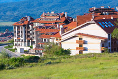 Wooden chalet hotel houses and summer mountains panorama in bulgarian ski resort Bansko, Bulgaria Stock Photos