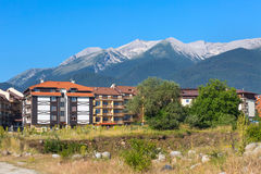 Wooden chalet hotel houses and summer mountains panorama in bulgarian ski resort Bansko, Bulgaria Stock Photography
