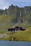 Wooden chalet under the summit on the shores of blue mountain lake. Stock Image