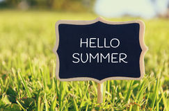 Wooden chalkboard sign with quote: HELLO SUMMER. In the forest, garden or park stock photography