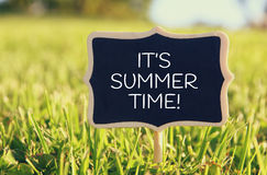 Wooden chalkboard sign with quote: IT'S SUMMER TIME. In the forest, garden or park Stock Photos