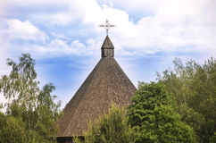 Wooden Chapel with cross. Wooden chapel of church seen through the trees Stock Image