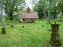Wooden chapel at the old cemetery surrounded by beautiful old tombstones and crosses. Bieszczady Mountains, Carpathians, Poland Royalty Free Stock Image