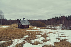 Wooden chapel in spring field. Royalty Free Stock Photo