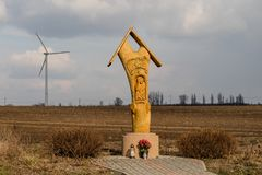 Wooden chapel standing near the road, Europe. A shrine with a wi. Nd turbine in the background. Season of the spring Stock Photo