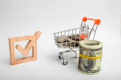 Wooden checkbox and a cart with coins. Attracting resources and resources to solve problems. Investment climate. Legislative prote royalty free stock photography