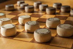 Wooden checkerboard with checkers spaced on table closeup Stock Image