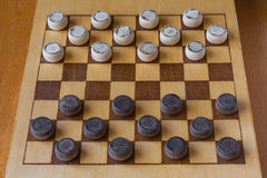 Wooden checkerboard with checkers spaced on table Stock Photo