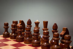 Wooden chess board and chessmen in black on a gray background Stock Image