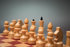 Wooden chess board and chessmen of white color on a gray background Stock Images