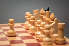 Wooden chess board and chessmen of white color on a gray background Royalty Free Stock Photography