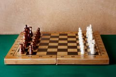 Wooden chess board with figures on green table Stock Image