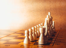 Wooden chess board with figures on green table Royalty Free Stock Images