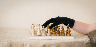 wooden chess board with figures and human hand in black glove Stock Photos