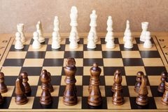 Wooden chess board with figures on table Stock Photography