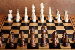Wooden chess board with figures on table Stock Images