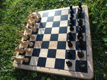 Wooden chess board on the grass. Outdoors game of chess Royalty Free Stock Photo