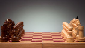Wooden chess board and pieces on a black background Stock Photography